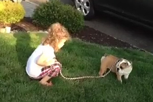 Little girl teaches dog how to poop